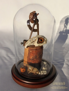 Rabbit Skull, Glass Eye, 1920's compass, Cicada and Exoskeleton, Replica Foot skeleton, dice, wood.